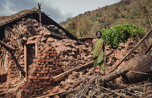 Image of an older woman standing on her collapsed house