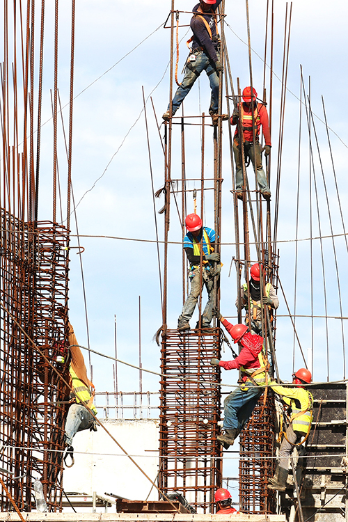 Image of a construction site and workers working hard